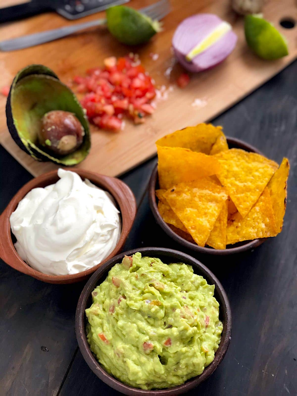 Guacamole, creme azedo e nachos fritos servidos em tigelas de barro, em vista de cima